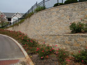 If you stand back from this mortarless retaining wall, it actually appears like rough cut stone. The manufacturer uses different pigments in the concrete mix and different sized stones to create the illusion.