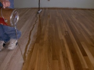 Pouring the urethane on the floor. The wide applicator can be seen in the background. PHOTO CREDIT: Roger R. Henthorn