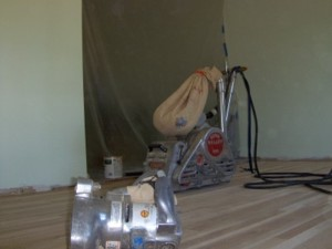 This floor sanding machine uses abrasive belts to sand the hardwood floors down to bare wood. The plastic hanging over the opening is to help control dust. PHOTO CREDIT: Roger R. Henthorn