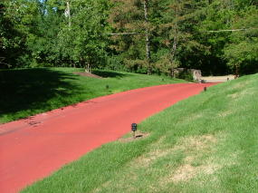 Your monitor is fine. This is a red blacktop driveway sealer applied by a professional driveway sealing company. Not only do they seal driveways, but they also seal tennis coursts on a regular basis. Start thinking outside the box if you want something other than a black driveway.  Photo Credit: Tim Carter