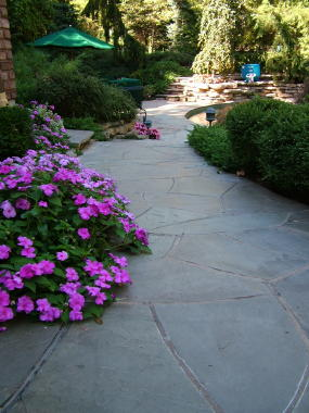 Curving the walkways and edges of the patio and then adding plants that flow over the stones makes for a luscious look.