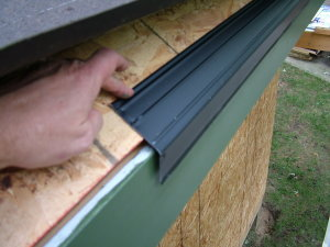 This critical drip-edge flashing is one of the first things that gets installed on top of the slanted wood roof sheathing. It is nailed directly to the bottom of the sloped roof and the roofing felt paper lays down on top of it. Note how the gutter board is already installed, painted and there is a slight gap between the flashing and the gutter board. PHOTO CREDIT: Tim Carter