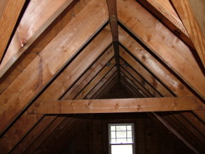 The slanted pieces of wood are actual roof rafters. The horizontal piece of wood is a collar tie. You can see how combined, all three pieces of wood make a strong triangle. This collar tie is not at the base of the rafters, yet it still imparts great strength. PHOTO CREDIT: Tim Carter