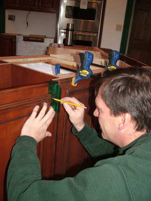 Master carpenter Bob Schmidt is using a handy template that tells him exactly where to drill the hole for the cabinet-knob screw. PHOTO CREDIT: Tim Carter
