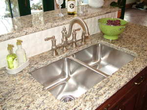 This stainless-steel undermount kitchen sink was installed in minutes with just some epoxy and hardware supplied by the sink manufacturer. PHOTO CREDIT: Tim Carter