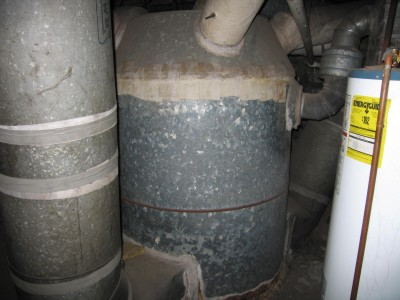 That off-white wrap on the top of the furnace and the pipes is asbestos! It used to be applied damp much like the old plaster-of-Paris casts on broken arms and legs. If you see white wrapping like this on your ducts do NOT disturb it. PHOTO CREDIT: Tony White