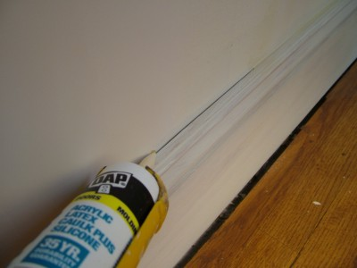 This ugly crack between the wall and baseboard will disappear once caulk fills the gap.  PHOTO CREDIT: Tim Carter