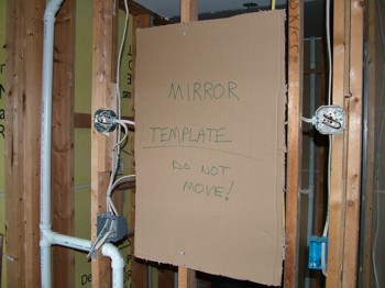 The piece of cardboard is the exact shape of the mirror that will be installed as soon as the room is finished. Using a template like this ensures the bathroom mirror lighting is installed perfectly. PHOTO CREDIT:  Tim Carter