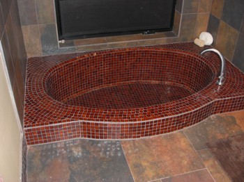 This unique bathroom tub is sunken into the floor and covered with tiny mosaic tile. PHOTO CREDIT:  Tim Carter