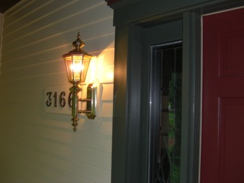 This outdoor sconce seems gigantic, but when viewed from a distance it's the perfect size for the door and porch. Note the custom mounting block behind the fixture. PHOTO CREDIT:  Tim Carter