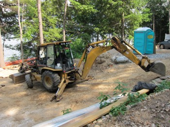 A smaller backhoe like this can be used to dig small basement and cellar holes but don't use them for big holes. These machines are really made for digging trenches. PHOTO CREDIT:  Tim Carter