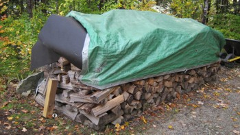 This firewood is protected from rain and snow. You can easily see the tar paper that covers the top of the firewood that's under the green tarp. PHOTO CREDIT:  Tim Carter