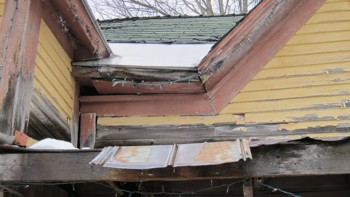 Wood rot is causing the center portion of the house to collapse and pull away from the left section. This is what's causing the giant opening just below the roof overhang.