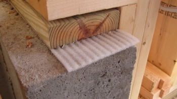 That funny ribbed foam between the wood and the poured concrete foundation is a gasket that prevents air leakage into a home.  Photo Credit: Tim Carter