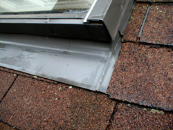 This is the sill flashing at the base of the skylight.  IT covers shingles that extend up under the flashing. You can also see step flashing on the side of the skylight that is laced into and under the shingles that abut the side of the skylight.